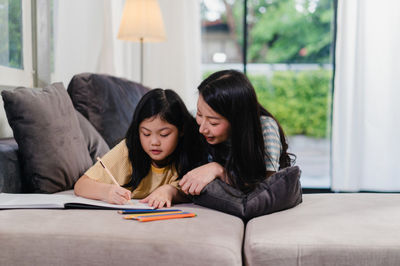 woman and girl doing homework